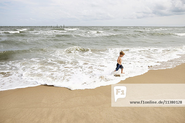 Caucasian boy running in waves at beach