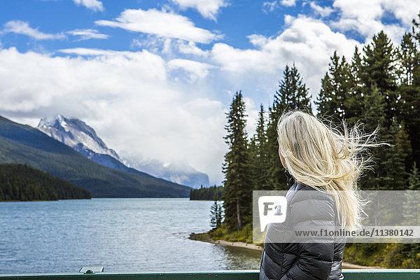 Caucasian woman standing near mountain lake