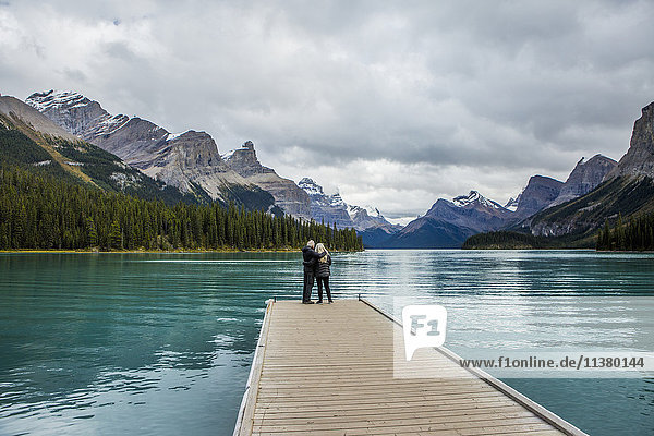 Caucasian couple standing at the end of dock on mountain lake