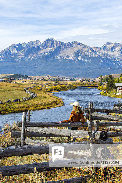 Caucasian woman leaning on wooden fence at mountain river