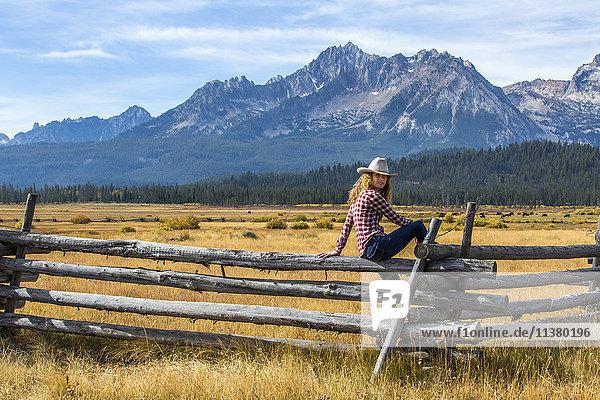 Caucasian woman sitting on wooden fence near mountain