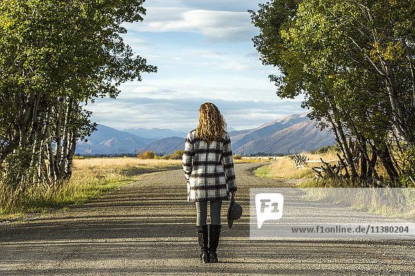 Caucasian woman standing on dirt road
