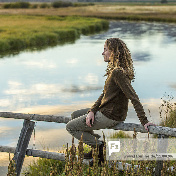 Caucasian woman sitting on wooden fence near river