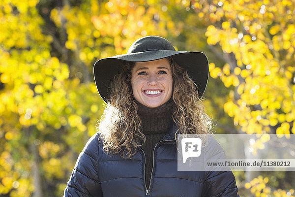Smiling Caucasian woman under autumn leaves