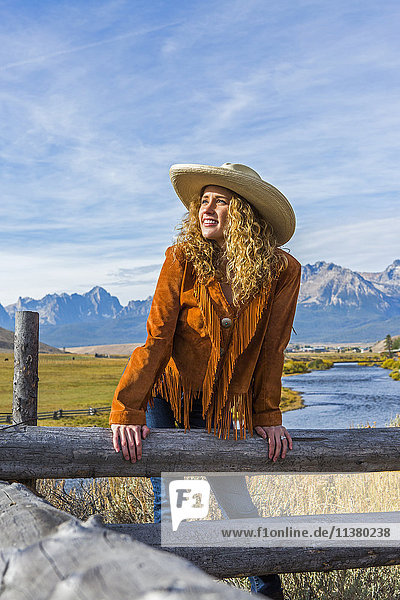 Caucasian woman leaning on wooden fence near mountain river