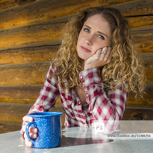 Bored Caucasian woman leaning table holding coffee cup