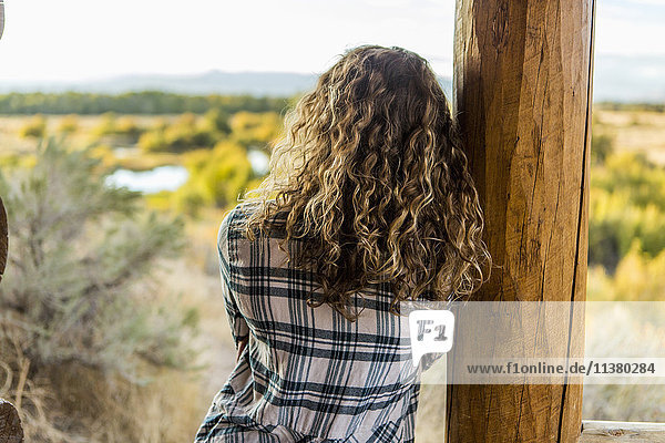 Caucasian woman leaning on wooden porch post