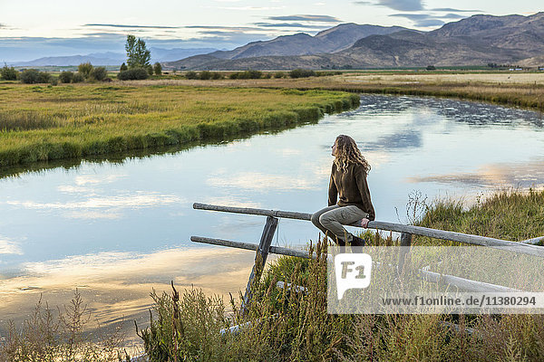 Caucasian woman sitting on wooden fence near mountain river