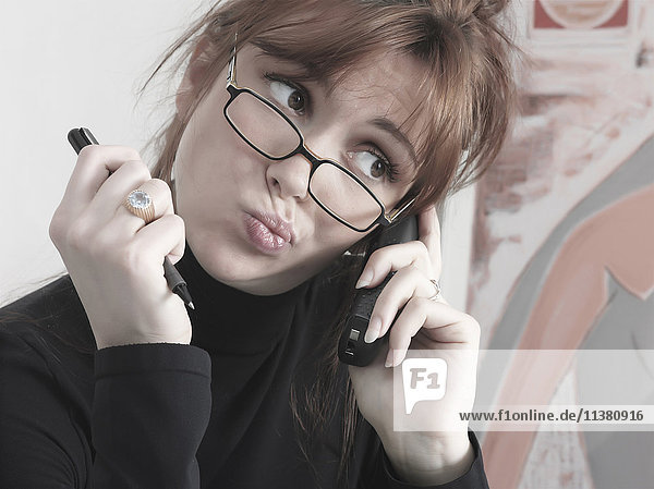 Caucasian businesswoman talking on telephone making a face