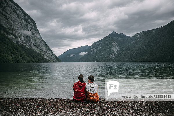 Caucasian couple sitting near mountain lake