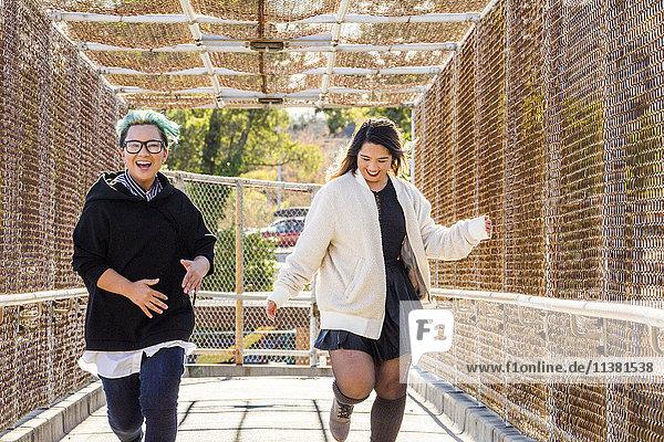 Smiling Asian women running on footbridge
