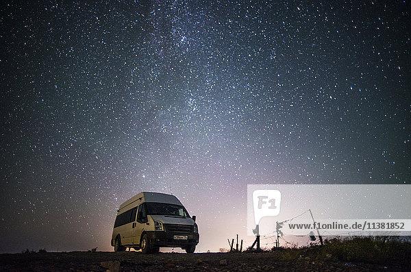 Camper van under starry sky