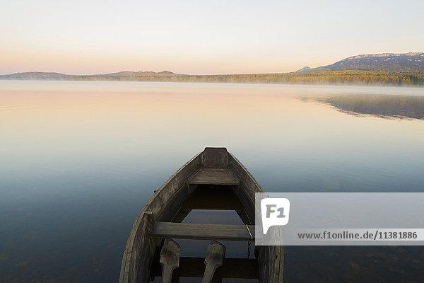 Empty rowboat on lake at sunset