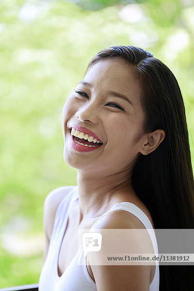 Portrait of laughing Asian teenage girl