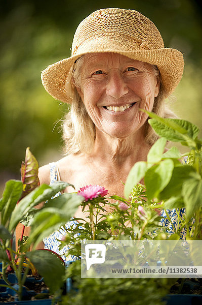 Portrait of smiling Caucasian woman holding tray of flowers