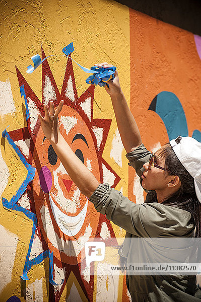 Woman removing painting tape from mural on wall
