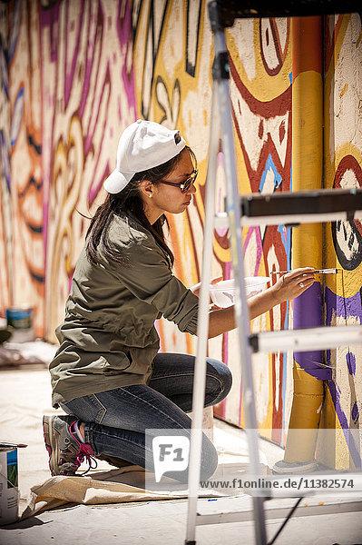 Woman kneeling on tarp painting mural on wall
