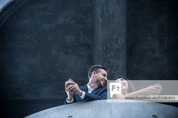 Low angle view of couple on balcony texting on cell phones