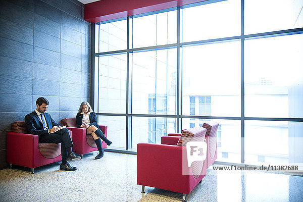 Businessman and businesswoman sitting in office lounge