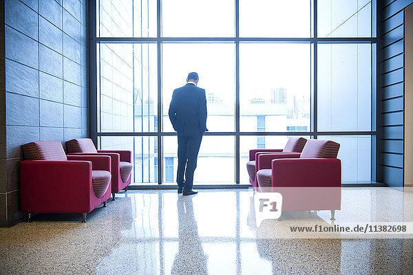 Hispanic businessman waiting in office lounge near window