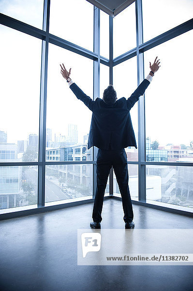 Hispanic businessman celebrating near window