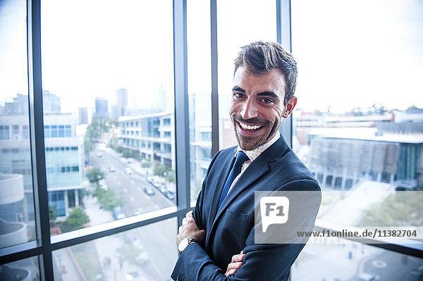 Portrait of smiling Hispanic businessman posing near window