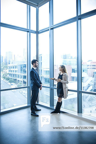 Businessman and businesswoman talking near window