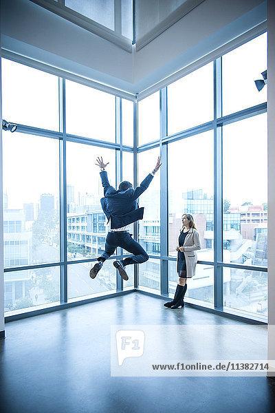Businesswoman watching businessman celebrating near window