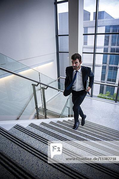 Hispanic businessman running on staircase