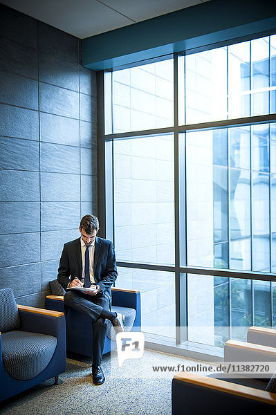 Hispanic businessman writing on notepad in office lounge