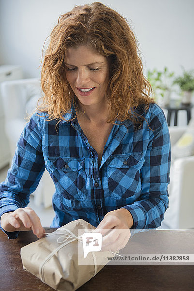 Caucasian woman tying string on package
