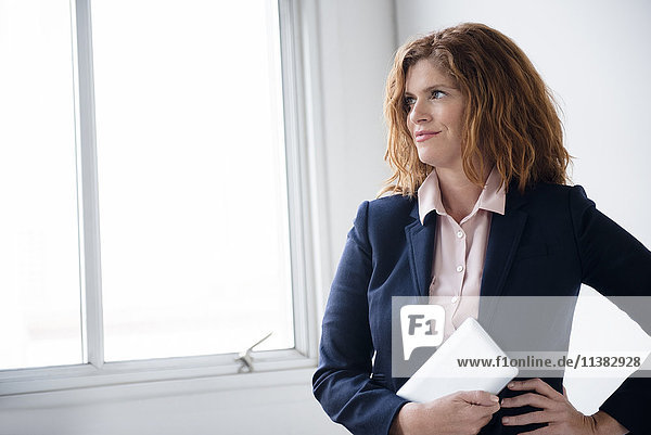 Smiling Caucasian businesswoman holding digital tablet near window