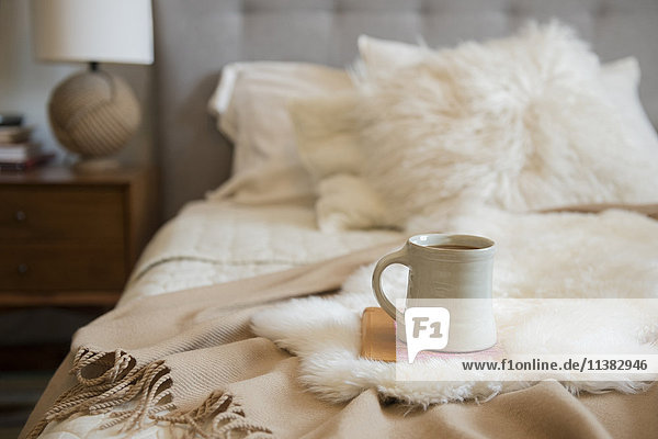 Coffee cup and book on fur on bed