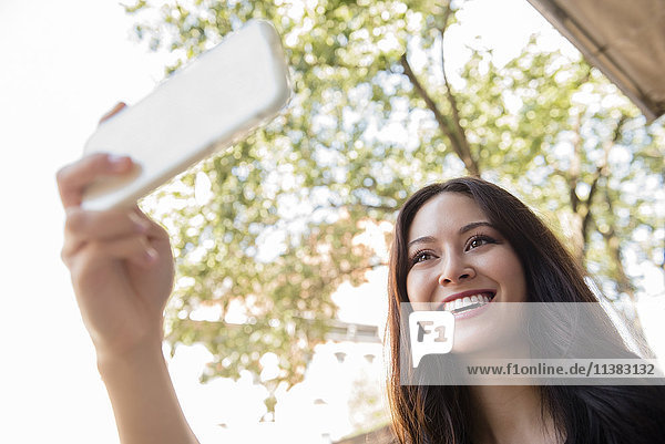 Smiling Thai woman posing for cell phone selfie