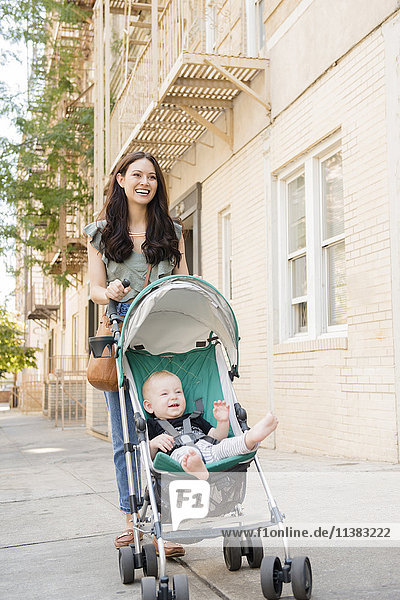 Mother pushing baby son in stroller in city