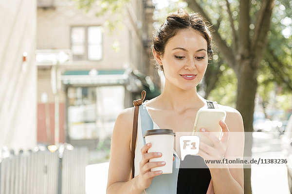 Thai woman holding coffee texting on cell phone in city