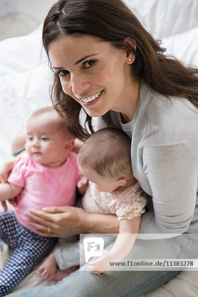 Caucasian mother sitting on bed holding twin baby daughters