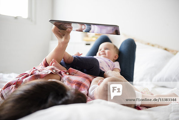 Caucasian mother on bed with twin baby daughters using digital tablet