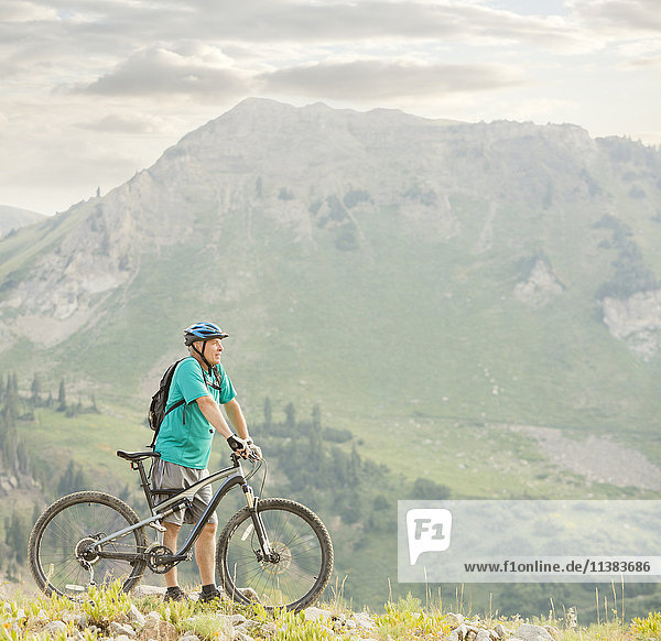 Caucasian man standing with mountain bike
