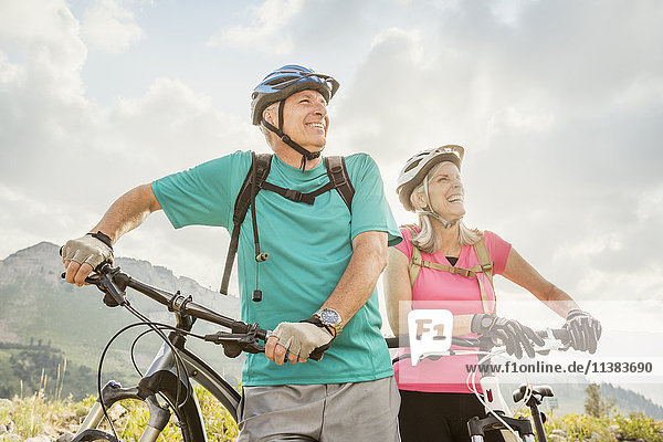 Caucasian couple standing with mountain bikes