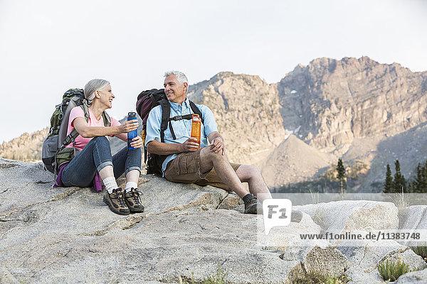 Caucasian couple resting on mountain