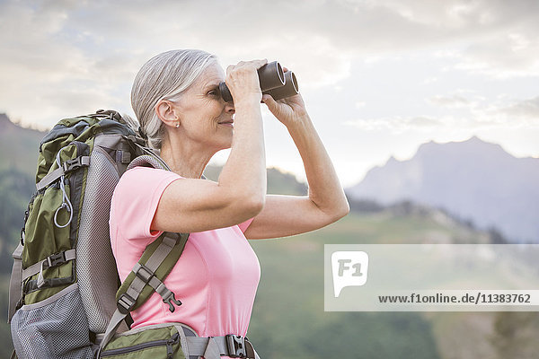 Caucasian woman hiking on mountain using binoculars