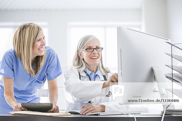 Caucasian doctor and nurse using computer at desk