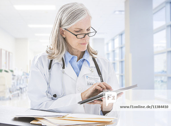 Caucasian doctor reading digital tablet in hospital