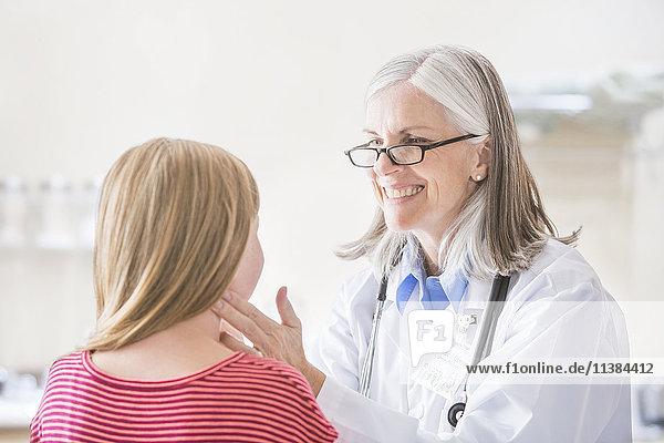 Caucasian doctor checking neck of girl