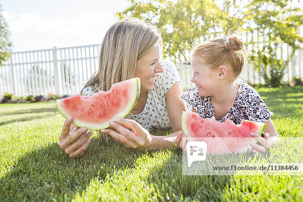 Caucasian mother and daughter laying in grass eating watermelon
