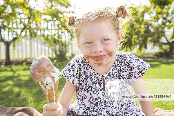 Caucasian girl with messy face eating ice cream cone