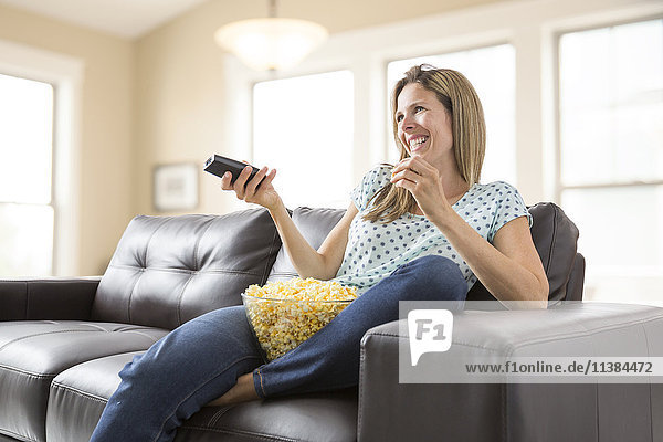 Caucasian woman watching television and eating bowl of popcorn