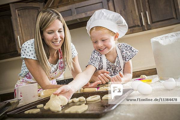 Caucasian mother and daughter baking cookies