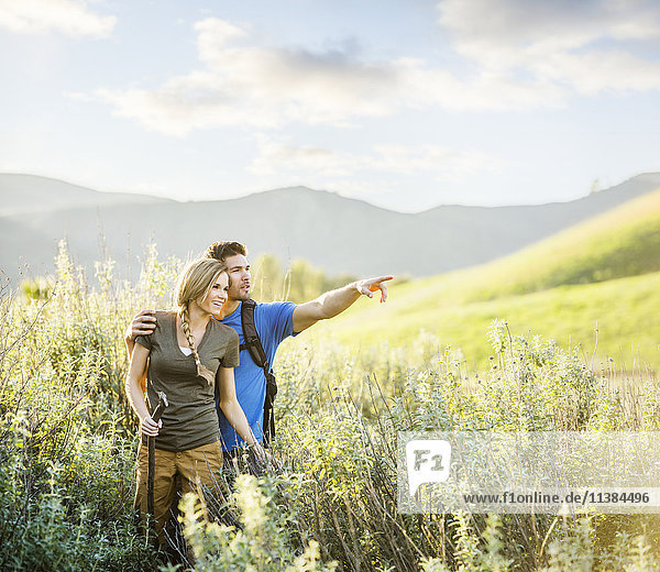 Caucasian couple hiking on hill